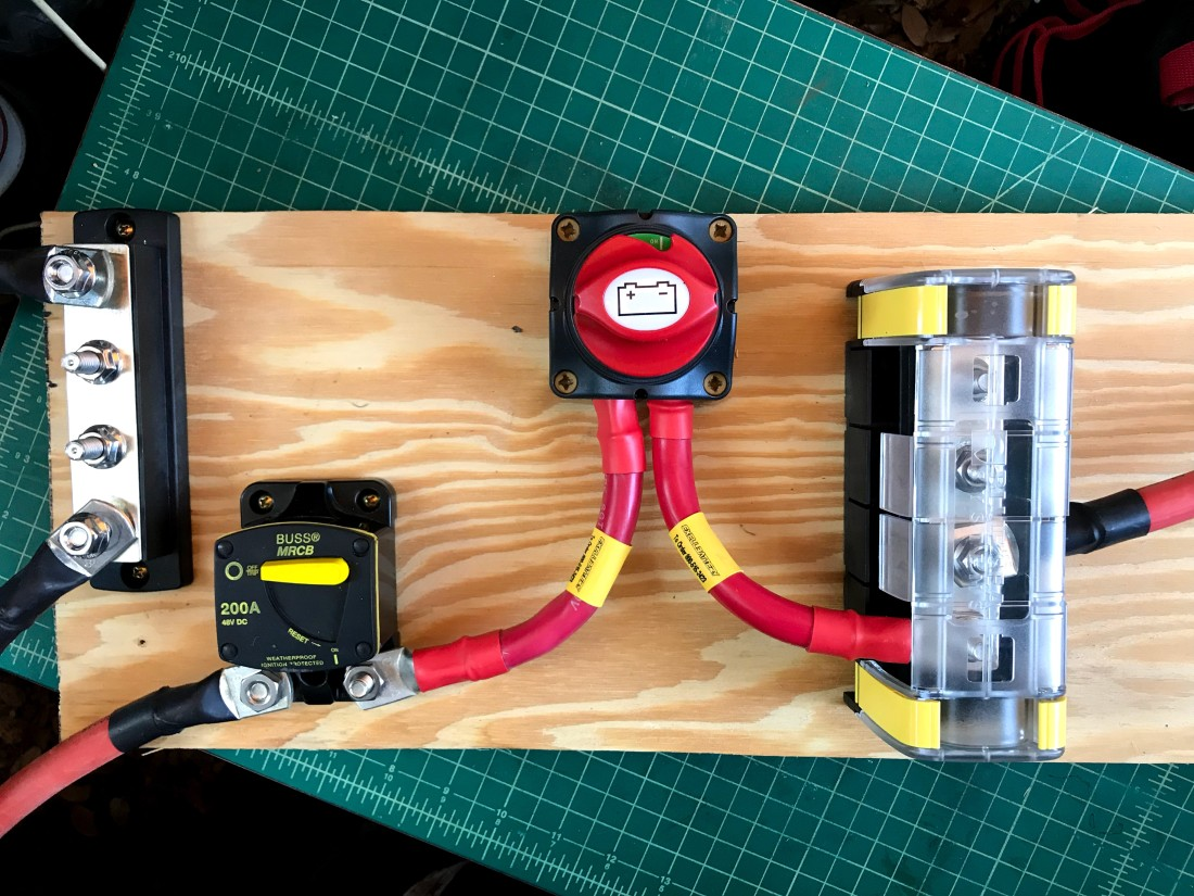 A  four post negative bus bar, 200 amp circuit breaker, battery cutoff switch, and 4 post positive bus bar with plastic cover are arranged left-to-right on and secured to a piece of plywood. Heavy 2/0 wires run between them. Red positive wires run to and from the breaker, cuttoff switch, and positive bus bar. Black negative wires run to the negative bus bar.